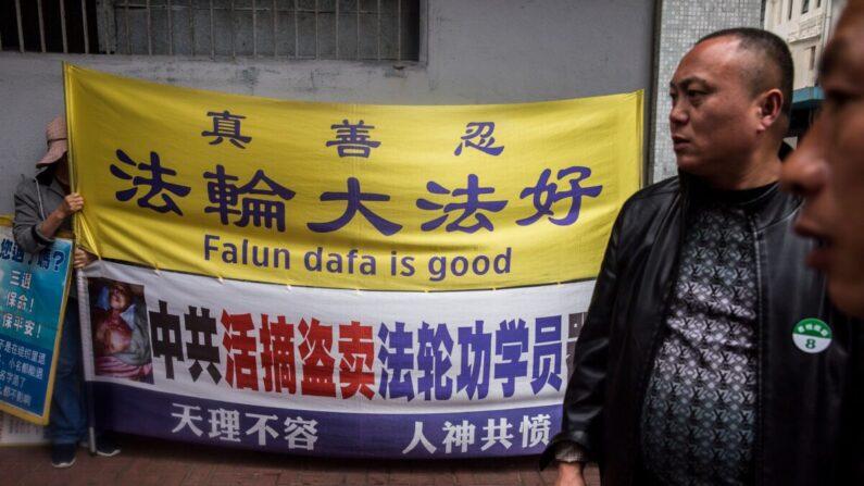 Una practicante de Falun Gong (izq.) sostiene un cartel junto a unos hombres de un grupo de turistas de China continental en el distrito de Kowloon de Hong Kong el 6 de enero de 2019. (Isaac Lawrence/AFP a través de Getty Images)