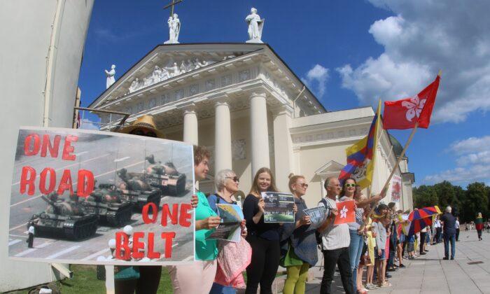 """Un grupo de personas participa en una protesta con una cadena humana en apoyo de la Vía de Hong Kong, una recreación de una protesta prodemocracia de la """"Vía Báltica"""" contra el gobierno soviético hace tres décadas, en Vilna, Lituania, el 23 de agosto de 2019. (Petras Malukas/AFP vía Getty Images)"""