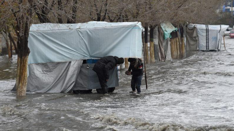En una foto de archivo, los vendedores tratan de asegurar su puesto en una calle inundada después de una fuerte lluvia en Kabul, Afganistán, el 15 de noviembre de 2020. (Wakil Kohsar/AFP vía Getty Images)