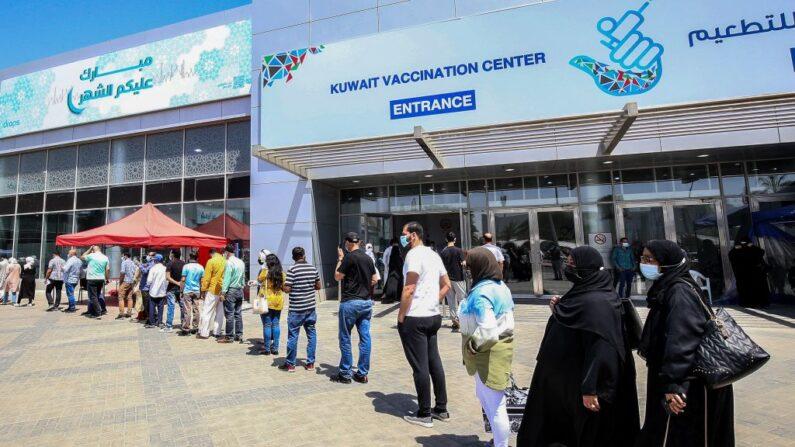 La gente hace cola mientras espera su turno para recibir vacuna contra el covid-19, frente al centro de vacunación improvisado, en el recinto ferial internacional de Kuwait en la ciudad de Kuwait, el 18 de abril de 2021. (Yasser Al-Zayyat/AFP vía Getty Images)