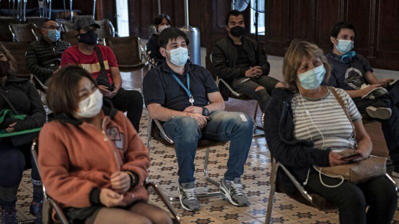 La gente espera su turno para ser vacunada con la vacuna china CoronaVac contra el COVID-19 en un centro de vacunación en Santiago, Chile, el 22 de abril de 2021. (Martin Bernetti / AFP vía Getty Images)