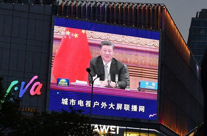 Los peatones esperan en una intersección mientras se ve en una pantalla gigante el informe de un programa de noticias sobre la aparición del presidente chino Xi Jinping en una cumbre sobre el clima liderada por Estados Unidos, en Beijing, el 23 de abril de 2021. (GREG BAKER/AFP vía Getty Images)