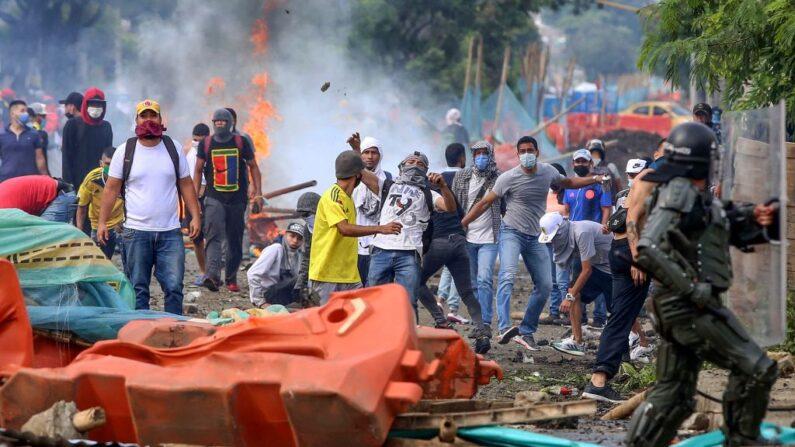 Manifestantes chocan con la policía antidisturbios durante una protesta contra el proyecto de reforma fiscal lanzado por el presidente colombiano Iván Duque, en Cali, Colombia, el 29 de abril de 2021. (Paola Mafla/AFP vía Getty Images)