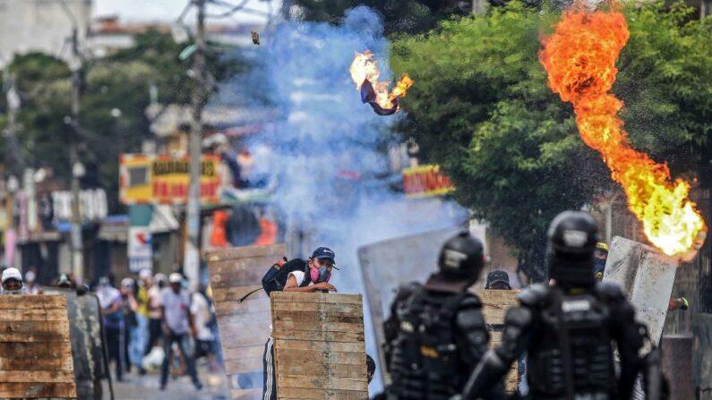 Manifestantes chocan con la policía antidisturbios durante una protesta contra el proyecto de reforma tributaria lanzado por el presidente colombiano Iván Duque, en Cali, Colombia, el 29 de abril de 2021. (Paola Mafla/AFP vía Getty Images)
