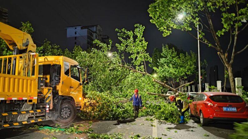 Esta foto tomada el 30 de abril de 2021 muestra a trabajadores retirando árboles caídos en Nantong, en la provincia oriental china de Jiangsu, después de que una violenta tormenta azotara la ciudad dejando al menos 11 muertos. (STR/AFP vía Getty Images)