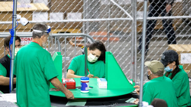 Unos empleados que trabajan para la empresa Cyber Ninjas, que fue contratada por el Senado del Estado de Arizona, examinan y recuentan las boletas de las elecciones generales de 2020, en el Veterans Memorial Coliseum, el 1 de mayo de 2021, en Phoenix, Arizona. (Courtney Pedroza/Getty Images)