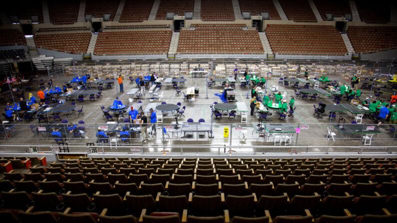 Contratistas que trabajan para Cyber Ninjas, empresa contratada por el Senado del estado de Arizona, examinan y vuelven a contar las boletas de las elecciones generales de 2020 en el Veterans Memorial Coliseum el 1 de mayo de 2021 en Phoenix, Arizona. (Courtney Pedroza/Getty Images)