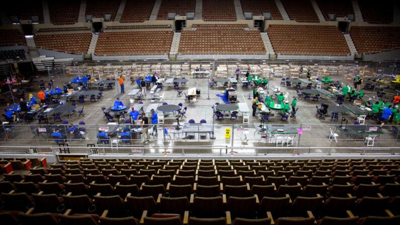 Los contratistas que trabajan para Cyber Ninjas, empresa que fue contratada por el Senado del Estado de Arizona, examinan y vuelven a contar las boletas de las elecciones generales de 2020, en el Veterans Memorial Coliseum, el 1 de mayo de 2021, en Phoenix, Arizona.  (Courtney Pedroza/Getty Images)