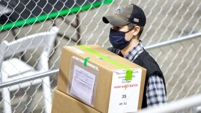 Un empleado que trabaja para la empresa Cyber Ninjas, que fue contratada por el Senado del Estado de Arizona, transporta boletas de las elecciones generales de 2020 en el Veterans Memorial Coliseum el 1 de mayo de 2021 en Phoenix, Arizona. (Courtney Pedroza/Getty Images)