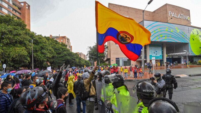 Manifestantes sostienen una bandera colombiana frente a una línea de policías antidisturbios durante una protesta contra un proyecto de ley de reforma tributaria frente a la casa del presidente colombiano Iván Duque en Bogotá el 1 de mayo de 2021. (Juan Barreto/AFP vía Getty Images)