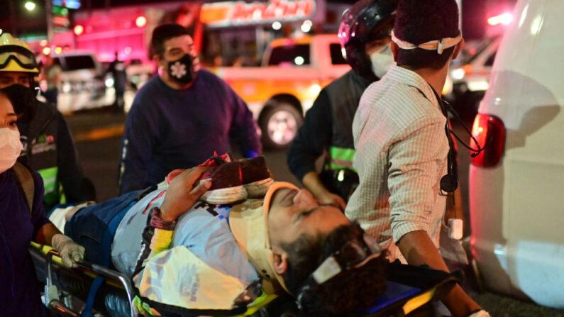Trabajadores de emergencia llevan a una persona herida en una camilla después de que un paso elevado para un metro se derrumbó parcialmente en la Ciudad de México el 3 de mayo de 2021. (PEDRO PARDO/AFP via Getty Images)