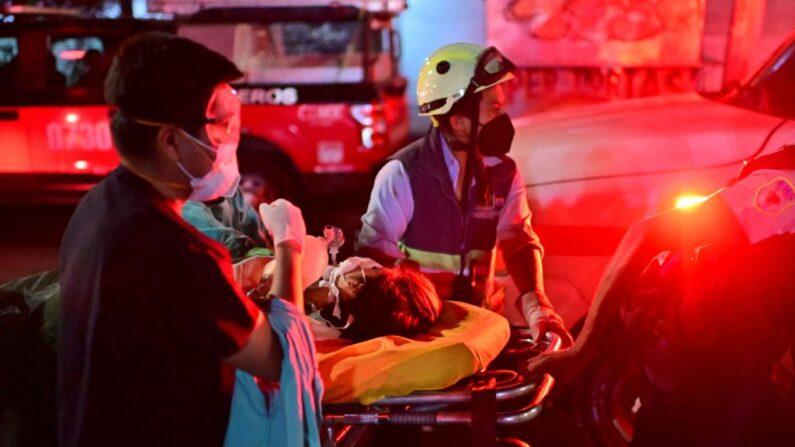 Trabajadores de emergencia trasladan a una persona herida en una camilla en el lugar de un accidente de tren después de que una línea de metro elevado se derrumbó en la Ciudad de México, México, el 4 de mayo de 2021. (Pedro Pardo/AFP vía Getty Images)