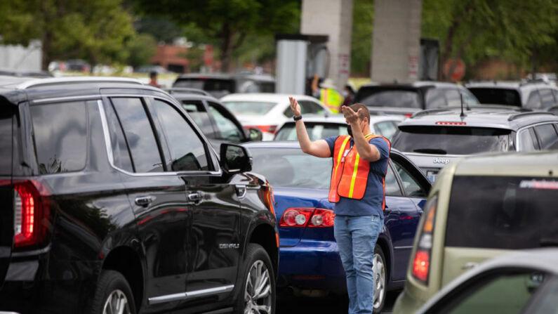 Los empleados dirigen a los coches a los surtidores de gasolina mientras estos hacen fila para llenar sus depósitos en un Costco de Tyvola Road, en Charlotte, Carolina del Norte, el 11 de mayo de 2021, tras el ataque de ransomware que dejó fuera de servicio al Colonial Pipeline. (LOGAN CYRUS/AFP a través de Getty Images)