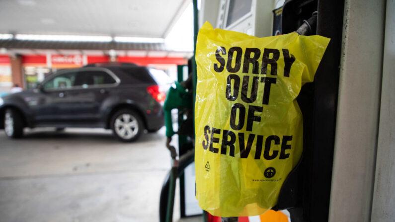 """Una bolsa que dice """"Fuera de Servicio"""" cubre un dispensador de gasolina mientras los coches siguen haciendo fila para poder llenar sus depósitos, cerca de la zona alta de Charlotte, Carolina del Norte, el 11 de mayo de 2021. (LOGAN CYRUS/AFP a través de Getty Images)"""
