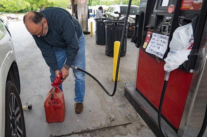 Un hombre llena un depósito de gasolina mientras los coches hacen fila, en un QuickTrip, el 11 de mayo de 2021, en Atlanta, Georgia. (Megan Varner/Getty Images)