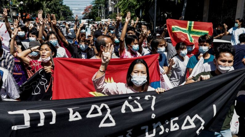 En esta foto tomada el 11 de mayo de 2021, los manifestantes hacen el saludo de tres dedos mientras marchan durante una manifestación contra el golpe militar en Rangún (Birmania). (STR/AFP vía Getty Images)