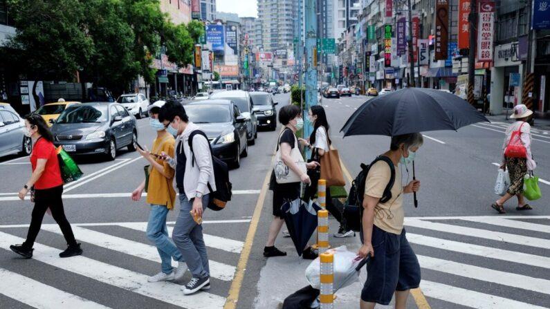 Los peatones llevan mascarillas tras una nueva ola de COVID-19 en la ciudad de Nuevo Taipei el 15 de mayo de 2021. (Sam Yeh/AFP vía Getty Images)