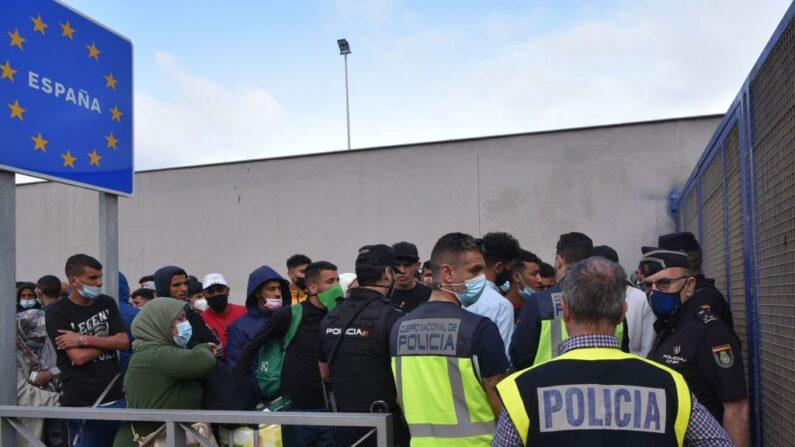 Policías españoles junto a migrantes que esperan cruzar la frontera con Marruecos en el enclave español de Ceuta el 20 de mayo de 2021. (Antonio Sempere / AFP vía Getty Images)