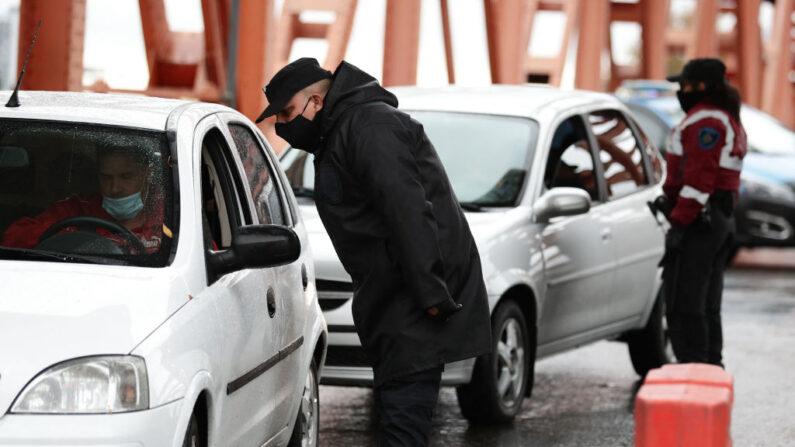 Un agente de tráfico y una mujer policía detienen a los coches en un puesto de control en un puente durante el primer día de un bloqueo impuesto por el Gobierno argentino, en Buenos Aires, el 22 de mayo de 2021. (Alejandro Pagni/AFP vía Getty Images)