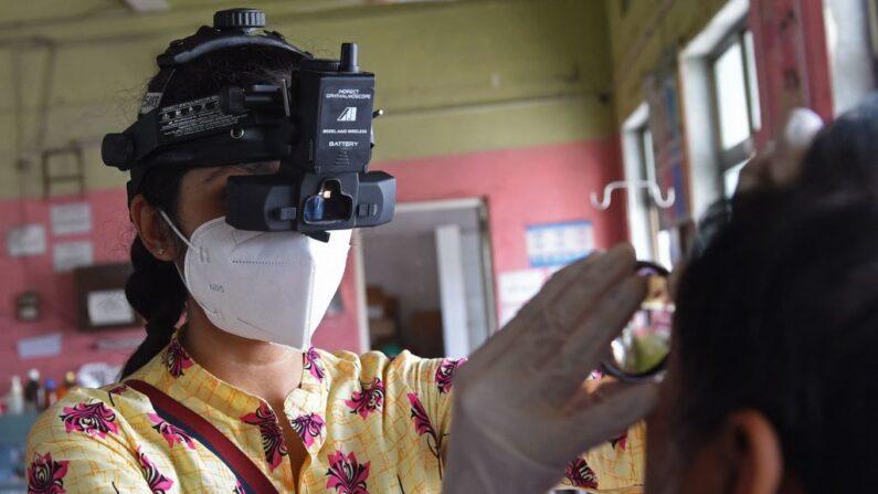 Una médico examina a un paciente infectado por el hongo negro o científicamente conocido como Mucormicosis, una infección fúngica mortal, en un hospital civil de Ahmedabad (India) el 23 de mayo de 2021. (Sam Panthaky/AFP vía Getty Images)