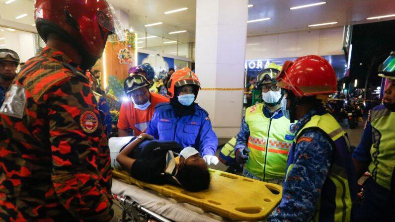 Esta imagen tomada el 24 de mayo de 2021 muestra al personal de rescate atendiendo a un pasajero herido en el exterior de la estación KLCC tras un accidente en el que se vieron implicados dos trenes de Light Rail Transit (LRT) en Kuala Lumpur (Malaysia). (STR/AFP vía Getty Images)