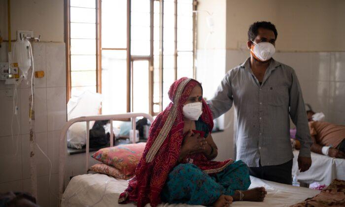 Un pariente consuela a una paciente de la India mientras recibe oxígeno suplementario durante el tratamiento para el coronavirus en el Hospital Gubernamental de Kapil, que se convirtió en un centro de consulta y tratamiento de coronavirus que sirve a las aldeas de los distritos de Jaipur y Sikar, el 15 de mayo de 2021 en Neem Ka Thana, Sikar, Distrito, Rajasthan, India. (Rebecca Conway/Getty Images)
