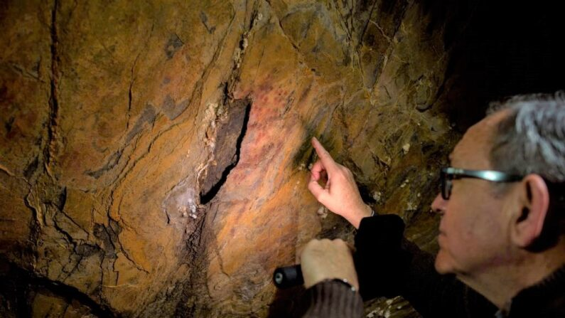 Pedro Cantalejo, director de la cueva andaluza de Ardales, observa pinturas rupestres en el interior de la caverna el 1 de marzo de 2018. (JORGE GUERRERO/AFP via Getty Images)The cave-paintings found in three caves in Spain, one of them in Ardales, were created between 43,000 and 65,000 years ago, 20,000 years before modern humans arrived in Europe, what could confirm that art was invented by the Neanderthals some 65,000 years ago. / AFP PHOTO / JORGE GUERRERO        (Photo credit should read JORGE GUERRERO/AFP via Getty Images)