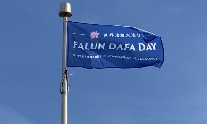 """Una bandera del """"Día de Falun Dafa"""" ondea en el aire tras ser izada el 8 de mayo de 2021 por el Ayuntamiento de Niagara Falls previo al Día Mundial de Falun Dafa en Niagara Falls, Canadá. (The Epoch Times)"""