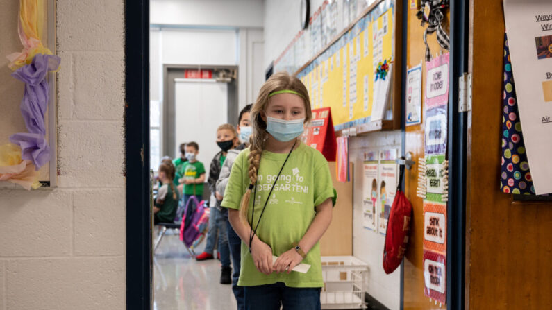 Los estudiantes con mascarillas esperan en una sola fila antes de dirigirse a la cafetería de una escuela primaria en Louisville, Ky., el 17 de marzo de 2021. (Jon Cherry/Getty Images)