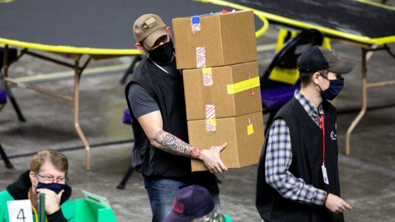 Unos empleados que trabajan para Cyber Ninjas, una empresa que fue contratado por el Senado de Arizona, examinan y recuentan boletas de las elecciones generales de 2020 en el Veterans Memorial Coliseum de Phoenix (Arizona) el 1 de mayo de 2021. (Courtney Pedroza/Getty Images)