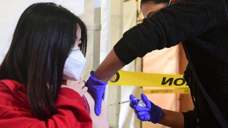 La estudiante de secundaria Kelly Zhou, de 17 años, recibe su primera vacuna COVID-19 de Pfizer, administrada por asistentes médicos del centro infantil y familiar St. John's Well en el instituto Abraham Lincoln de Los Ángeles, California, el 23 de abril de 2021. (Frederic J. Brown/AFP vía Getty Images)