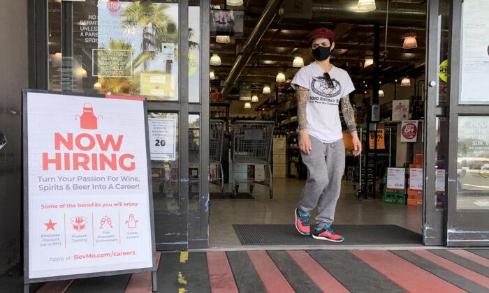 Un cliente camina junto a un cartel de ahora se contrata en una tienda BevMo en Larkspur, California, el 2 de abril de 2021. (Justin Sullivan/Getty Images)