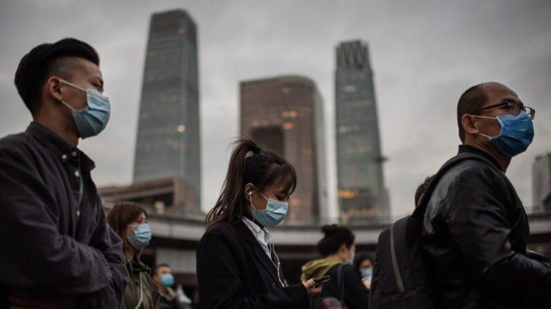 Personas con mascarillas como medida preventiva contra el COVID-19 esperan en un semáforo en rojo para cruzar una calle durante la hora pico en Beijing, el 14 de octubre de 2020. (Nicolas Asfouri/AFP vía Getty Images)