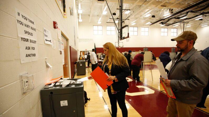 En esta foto de archivo se ve a una mujer colocando su papeleta en una máquina de tabulación después de votar. (Jeff Kowalsky/AFP vía Getty Images)