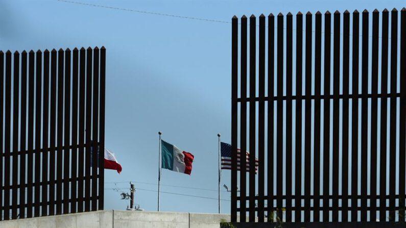 Fotografía de banderas a través del muro de seguridad cerca de McAllen, Texas (EE.UU.). EFE/Larry W. Smith/Archivo