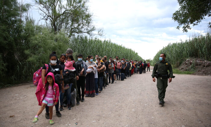 Un grupo de venezolanos espera a ser escoltado por la Patrulla Fronteriza tras cruzar ilegalmente el río Grande desde México hacia Del Río, Texas, el 3 de junio de 2021. (Charlotte Cuthbertson/The Epoch Times)