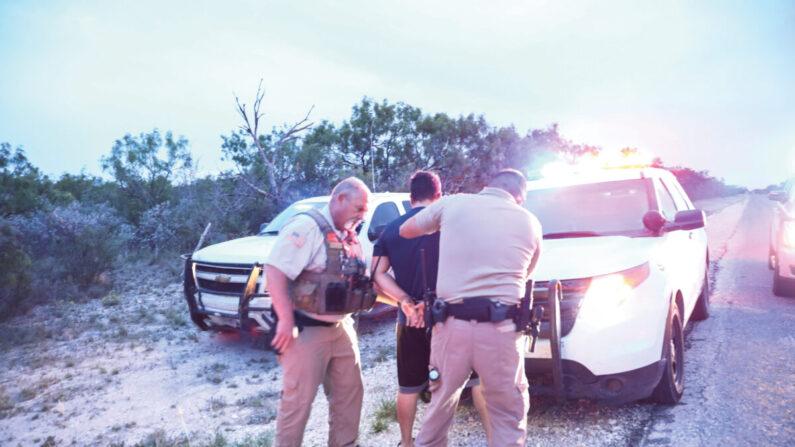 El alguacil del condado de Kinney Steve Gallegos y los agentes del alguacil del condado de Kinney arrestan a un contrabandista y a siete extranjeros ilegales de Guatemala cerca de Brackettville, Texas, el 25 de mayo de 2021. (Charlotte Cuthbertson/The Epoch Times)