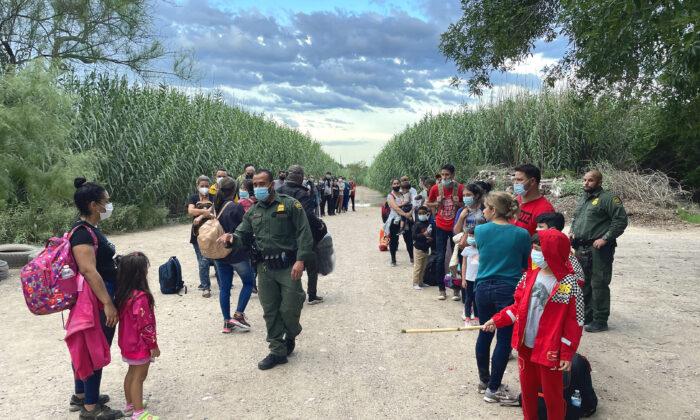 Un grupo de venezolanos espera ser recogido por la Patrulla Fronteriza después de cruzar ilegalmente el Río Grande desde México hacia Del Río, Texas, el 3 de junio de 2021. (Charlotte Cuthbertson/The Epoch Times)