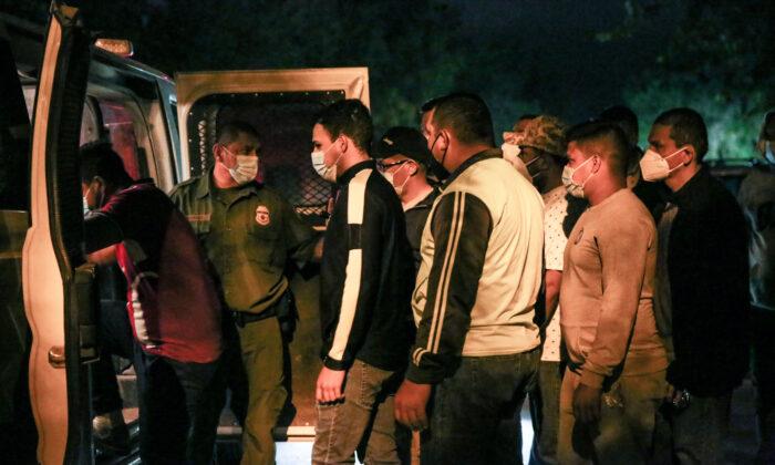 Agentes de la Patrulla Fronteriza detienen a inmigrantes ilegales tras cruzar el Río Grande desde México hacia Del Río, Texas, el 23 de mayo de 2021. (Charlotte Cuthbertson/The Epoch Times)