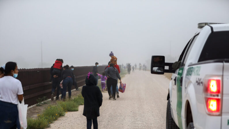 Un grupo de inmigrantes ilegales con la Patrulla Fronteriza tras cruzar la frontera entre Estados Unidos y México en La Joya, Texas, el 10 de abril de 2021. (Charlotte Cuthbertson/The Epoch Times)
