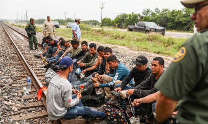 Agentes de la Patrulla Fronteriza arrestan a 21 extranjeros ilegales de México que se habían escondido en una tolva de granos, en un tren de carga que se dirigía a San Antonio, cerca de Uvalde, Texas, el 21 de junio de 2021. (Charlotte Cuthbertson/The Epoch Times)
