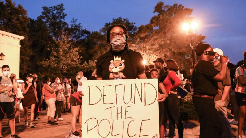 """Un manifestante sostiene un cartel de """"Desfinanciar a la Policía"""" durante una protesta cerca de la Casa Blanca tras la muerte de George Floyd el 25 de mayo bajo custodia policial, en Washington el 6 de junio de 2020. (Charlotte Cuthbertson/The Epoch Times)"""