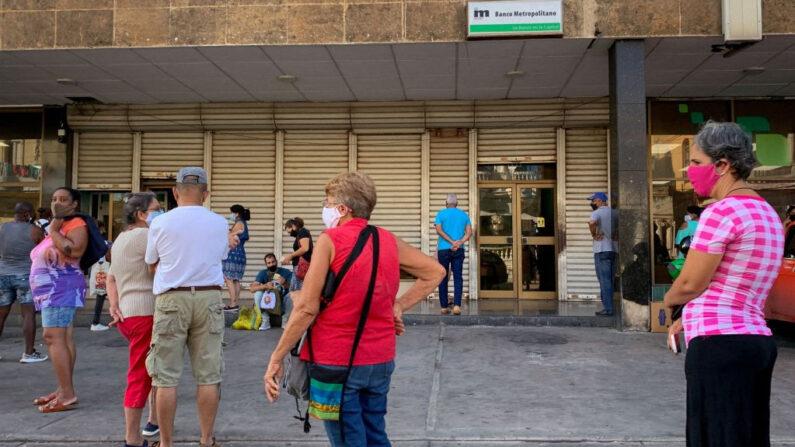 La gente hace cola frente a una sucursal bancaria en La Habana (Cuba) el 11 de junio de 2021, para depositar dólares estadounidenses antes de que el régimen ponga en vigor un nuevo decreto que suspenderá dichos depósitos en los bancos del país. (Adalberto Roque/AFP vía Getty Images)