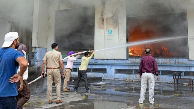 En una foto de archivo, los bomberos intentan sofocar un incendio en una fábrica de procesamiento de frutos secos en las afueras de Amritsar, India, el 7 de mayo de 2021. (Narinder Nanu / AFP vía Getty Images)