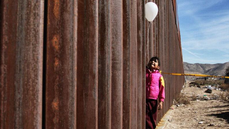 En una foto de archivo, una niña sostiene un globo blanco en el muro fronterizo entre México y Estados Unidos, el 10 de diciembre de 2017. (Herika Martinez/AFP vía Getty Images)