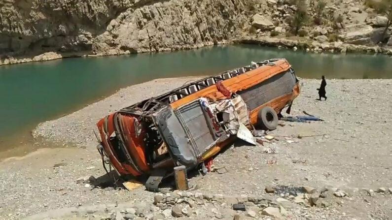 Un hombre pasa junto a un autobús dañado en el lugar del accidente en un remoto distrito de la provincia de Baluchistán (Pakistán) el 11 de junio de 2021. - Un autobús que transportaba a decenas de peregrinos se precipitó por un barranco en el suroeste de Pakistán el 11 de junio, causando la muerte de al menos 20 pasajeros, según las autoridades. (AFP vía Getty Images)