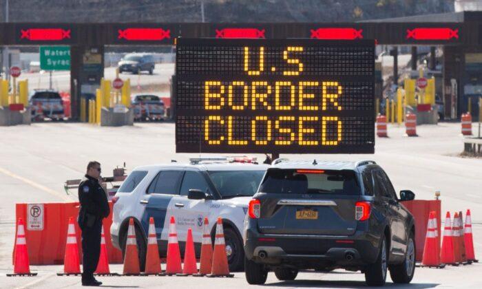 Funcionarios de aduanas de EE.UU. hablan con personas en un automóvil, junto a un letrero que dice que la frontera entre EE.UU. y Canadá está cerrada, en Lansdowne, Ontario, Canadá, el 22 de marzo de 2020. (Lars Hagberg/AFP vía Getty Images)