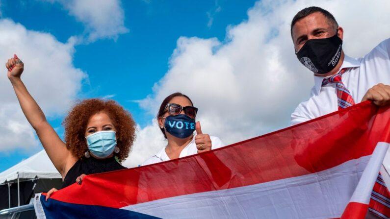 Hispanos sostienen la bandera puertorriqueña en Orlando, Florida, el 27 de octubre de 2020. (RICARDO ARDUENGO/AFP a través de Getty Images)