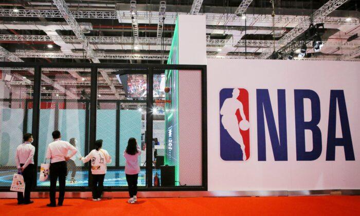 La gente se mantiene junto a un logotipo de la NBA en la Exposición de la NBA en la 3ra Exposición Internacional de Importaciones de China (CIIE) en Shanghai, China, el 5 de noviembre de 2020. (STR/AFP a través de Getty Images)