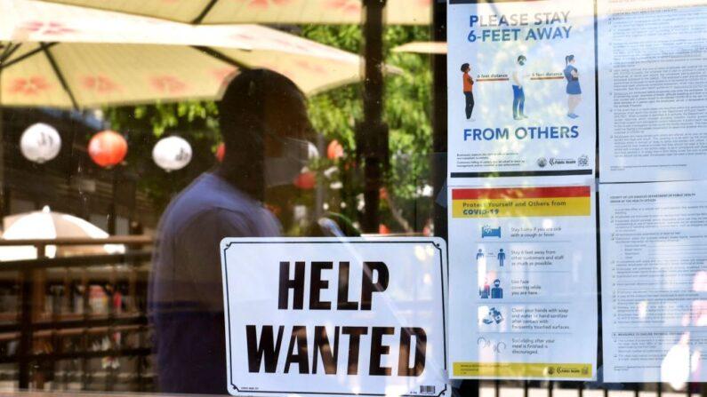 Un anuncio de empleo se coloca junto a las directrices de seguridad sobre el coronavirus frente a un restaurante en Los Ángeles, California, el 28 de mayo de 2021. (FREDERIC J. BROWN/AFP vía Getty Images)